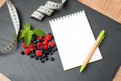 Blueberries, raspberries, mint, measuring tape and notepad for writing notes or resolutions, concept of sport, diet. Slimming, detox, healthy lifestyles and Royalty Free Stock Photography