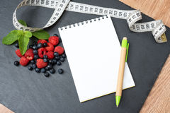 Blueberries, raspberries, mint, measuring tape and notepad for writing notes or resolutions, concept of sport, diet. Slimming, detox, healthy lifestyles and Stock Photography
