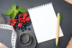 Blueberries, raspberries, mint, measuring tape and notepad for writing notes or resolutions, concept of sport, diet. Slimming, detox, healthy lifestyles and Stock Photos