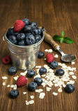 Blueberries , raspberries and oatmeal in a bucket. On a wooden background Royalty Free Stock Photo