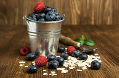 Blueberries , raspberries and oatmeal in a bucket. On a wooden background Royalty Free Stock Image