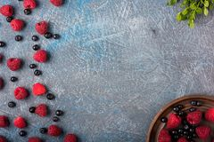 Blueberries and raspberries in an old-fashioned container on a gray concrete background stock image