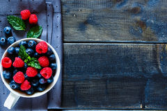 Blueberries and raspberries. Old wooden table with assortment berries blueberries and raspberries at textile napkin over dark textured background. Top view Stock Images