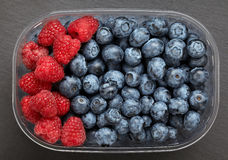 Blueberries and raspberries. In plastic container closeup top view Stock Photography