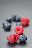 Blueberries and raspberries on slate surface. Closeup photo Royalty Free Stock Photo