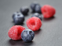 Blueberries and raspberries on slate surface. Closeup photo Royalty Free Stock Photography