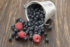 Blueberries and raspberries in a small bucket. Scattered on a wooden brown table Royalty Free Stock Photography
