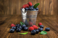 Blueberries and raspberries in a small bucket. On wooden Royalty Free Stock Images
