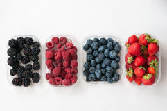 Blueberries raspberries strawberries blackberries. On a white background in white bowls of fresh, juicy wild berries blueberries raspberries strawberries and royalty free stock images