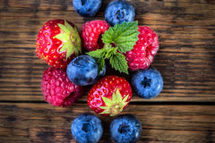 Blueberries, raspberries, strawberries on wooden background. Royalty Free Stock Images