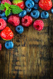 Blueberries, raspberries, strawberries on wooden background. Berry fruits on wooden background or table. Blueberries, raspberries, strawberries, Forest fruits Stock Photography