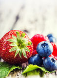Blueberries, raspberries, strawberries on wooden background. Stock Photography