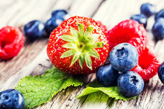 Blueberries, raspberries, strawberries on wooden background. Royalty Free Stock Photos