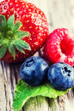 Blueberries, raspberries, strawberries on wooden background. Stock Image
