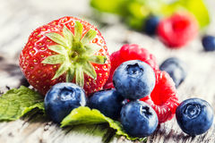 Blueberries, raspberries, strawberries on wooden background. Royalty Free Stock Photo