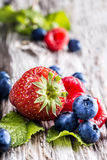 Blueberries, raspberries, strawberries on wooden background. Stock Images