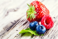 Blueberries, raspberries, strawberries on wooden background. Berry fruits on wooden background or table. Blueberries, raspberries, strawberries, Forest fruits stock photos