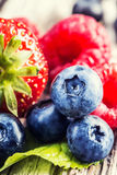 Blueberries, raspberries, strawberries on wooden background. Royalty Free Stock Photography