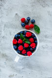 Blueberries and raspberries. White ceramic cup with assortment berries blueberries and raspberries over concrete textured background. Top view composing Stock Photography