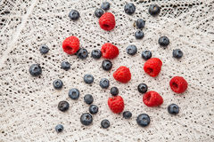 Blueberries and raspberries on a white lace tablecloth Stock Images