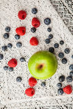 Blueberries and raspberries on a white lace tablecloth Royalty Free Stock Photo