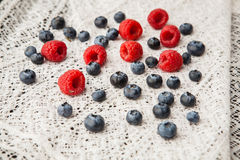 Blueberries and raspberries on a white lace tablecloth Stock Photography