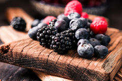 Blueberries and raspberries on a wooden background. Blueberries and raspberries on wooden background berry mix Stock Photos