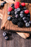 Blueberries and raspberries on a wooden background. Blueberries and raspberries on wooden background berry mix Royalty Free Stock Photo