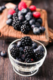 Blueberries and raspberries on a wooden background. Blueberries and raspberries on wooden background berry mix Royalty Free Stock Images