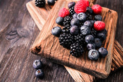 Blueberries and raspberries on a wooden background. Blueberries and raspberries on wooden background berry mix Stock Images
