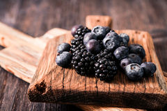 Blueberries and raspberries on a wooden background. Blueberries and raspberries on wooden background berry mix Stock Photo