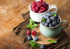 Blueberries and raspberries on a wooden background stock photos
