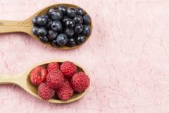 Blueberries and raspberries in a wooden spoon on a pink napkin. Healthy vegetarian food. Diet Royalty Free Stock Image