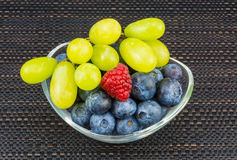 Blueberries, raspberry and grapes. Luscious fresh fruit in oval glass bowl royalty free stock photos