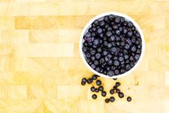 Blueberries in a rounded bowl on a wooden table royalty free stock image