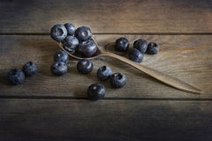 Blueberries in rustic kitchen setting with old wooden background Stock Photos