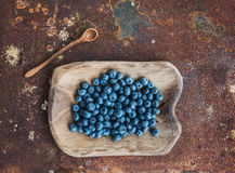 Blueberries in a rustic wooden serving dish over grunge metal rusty background. Top view royalty free stock photography