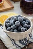 Blueberries served in a white plate on a table with lemons royalty free stock images