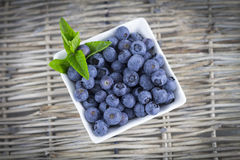 Blueberries. Several blueberries in a white cup with mint on straw Stock Images