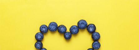 Style minimalism. Blueberries in the shape of heart on a yellow background. The concept: blueberries prevent heart disease Royalty Free Stock Image