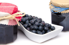 Blueberries in a small dish with two jars of blueberry jam Royalty Free Stock Images