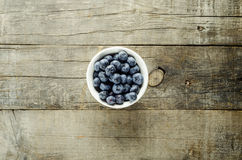 Blueberries. Solo top view shot of Blueberries on bowl on a rough textured wood royalty free stock photography