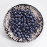 Blueberries. Some blueberries in an antique plate stock image