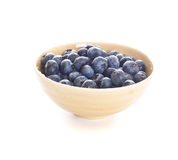 Blueberries spilling out of a bowl. Blueberries spilling out of a pottery bowl royalty free stock photography