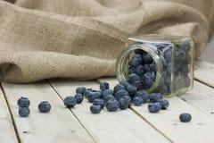 Blueberries spilt from a jar Stock Photos