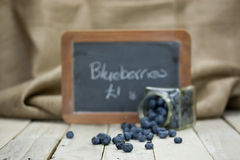 Blueberries spilt from a jar Stock Images