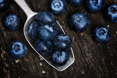 Blueberries on spoon, old wooden board Stock Photography