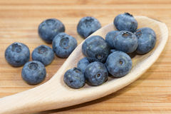 Blueberries in spoon on wooden background Royalty Free Stock Images