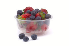 Blueberries and strawberries in a basket. On white background Royalty Free Stock Images