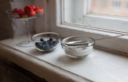 Blueberries strawberries icing sugar in a small bowl at the window Stock Photos